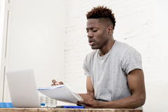 African american man sitting at home living room working with laptop computer and paperwork Royalty Free Stock Images