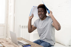 African american man sitting at home living room working with laptop computer and paperwork. Young attractive african american man sitting at home living room royalty free stock photography