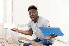 African american man sitting at home living room working with laptop computer and paperwork Royalty Free Stock Photography