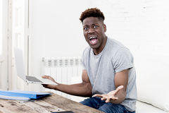 African american man sitting at home living room working with laptop computer and paperwork. Young attractive african american man sitting at home living room Royalty Free Stock Photo