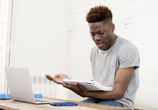 African american man sitting at home living room working with laptop computer and paperwork Royalty Free Stock Image