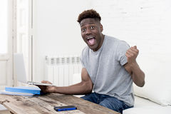 African american man sitting at home living room working with laptop computer and paperwork Stock Images