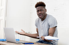 African american man sitting at home living room working with laptop computer and paperwork. Young attractive african american man sitting at home living room stock images