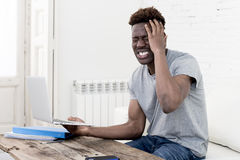 African american man sitting at home living room working with laptop computer and paperwork. Young attractive african american man sitting at home living room royalty free stock image