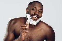 African American man smears shaving cream stock photos