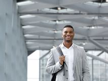 African american man smiling with bag at airport Royalty Free Stock Photography