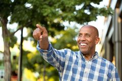 African American man smiling and pointing away from the camera. Stock Photos