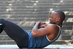 African american man sport training workout sit ups outside stock photo