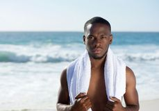 African american man standing at the beach with towel Stock Photos