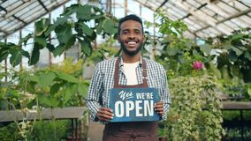 African American man standing in greenhouse with we are open sign smiling. African American man is standing in greenhouse with we are open sign smiling looking stock footage