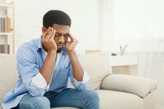 African-american man suffering from headache at home. Upset african-american man squeezing head with hands, writhing in pain, suffering from headache at home royalty free stock image