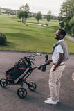 African american man in sunglasses walking with bag full of golf clubs. Smiling african american man in sunglasses walking with bag full of golf clubs Stock Photos