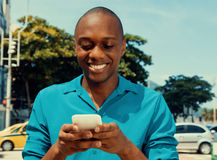 African american man surfing the internet by phone outdoor in a warm cinema look Stock Photos