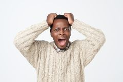 african american man in sweater in panic, shocked to hear bad news. Stressful situation concept stock photo