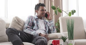 Relaxed man talking on mobile phone at home. African american man talking on mobile phone while relaxing on sofa at home stock footage