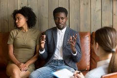 African-american man talking to family counselor, black couple a. African men talking to family counselor, frustrated husband sharing marital problems while royalty free stock photo