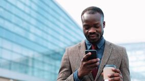 African American man types something in his smartphone walking outside. Businesman walks down the airport terminal, uses. His phone, drink coffee, print the stock video