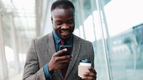 African American man types something in his smartphone walking outside. Businesman walks down the airport terminal, uses. His phone, drink coffee, print the stock video footage