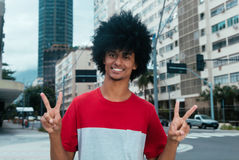 African american man with typical afro hair showing victory sign. Outdoor in the city Stock Photography