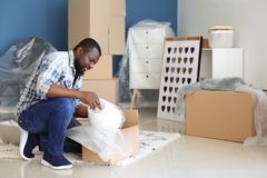 African-American man unpacking box indoors. Moving into new house royalty free stock photos