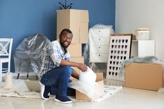 African-American man unpacking box indoors. Moving into new house stock photo