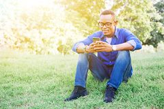 African American man using mobile phone in the park Royalty Free Stock Photo