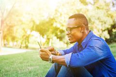 African American man using mobile phone in the park Royalty Free Stock Photos