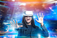 African American man in vr glasses playing game. Portrait of an African American man in a hoodie and vr glasses playing an exciting game. Concept of the future Stock Photo
