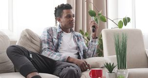 Man watching television in the living room. African american man watching television while relaxing on sofa in the living room stock video
