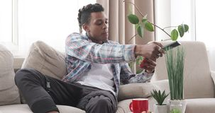 Man watching tv and using mobile phone at home. African american man watching tv and using mobile phone while having coffee at home stock video