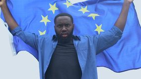 African-american man waving flag of European Union, human right, racial equality