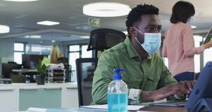 Man wearing face mask using computer at office