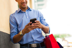African American Man Writing Message On Phone Shopping Bags Stock Photo