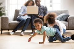 African American married couple using laptop while children play. African American married couple using laptop together, sitting on couch at new home while stock images