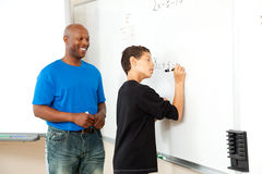 African American Math Teacher and Student. African American math teacher helping a student to pre-algebra on the board Stock Photo