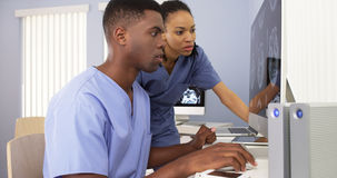 African American medical specialists working together on computer Royalty Free Stock Images