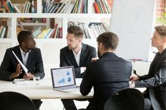 African american expressing ideas to coworkers on briefing. African american men expressing thoughts on financial issues and annual reports to caucasian royalty free stock photos