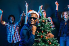 African american man hugging with cristmas tree Royalty Free Stock Image