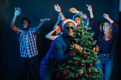 African american man hugging with cristmas tree Royalty Free Stock Photos