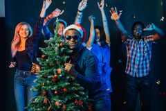 African american man hugging with cristmas tree Royalty Free Stock Photo