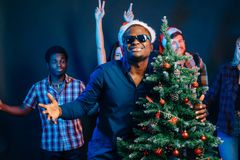 African american man hugging with cristmas tree Stock Image