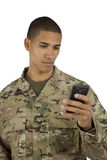 African American Military Man Texting. A soldier texts on his smartphone stock photos