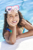 African American Mixed Race Girl Child In Swimming Pool. A cute happy young interracial African American girl child relaxing on the side of a swimming pool Royalty Free Stock Photography