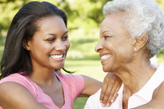 African American Mother And Adult Daughter Relaxing In Park Stock Photos