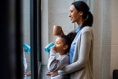 Mother and daughter drinking hot beverage. African american mother and daughter drinking hot beverage at window stock images