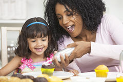 African American Mother Daughter Icing Cakes. African American mother and mixed race daughter having fun frosting icing cup cakes Stock Photos