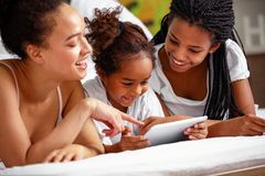 African American mother and daughters lying in the bed and using stock image