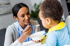 African american mother feeding baby. Smiling african american mother feeding little son with porridge at home Royalty Free Stock Photos