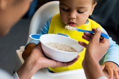 Little son eating porridge. African american mother feeding little son with porridge at home Royalty Free Stock Image