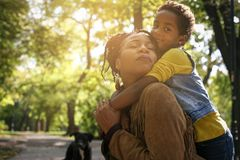 African American mother and her daughter enjoying in park together and hugging. stock image